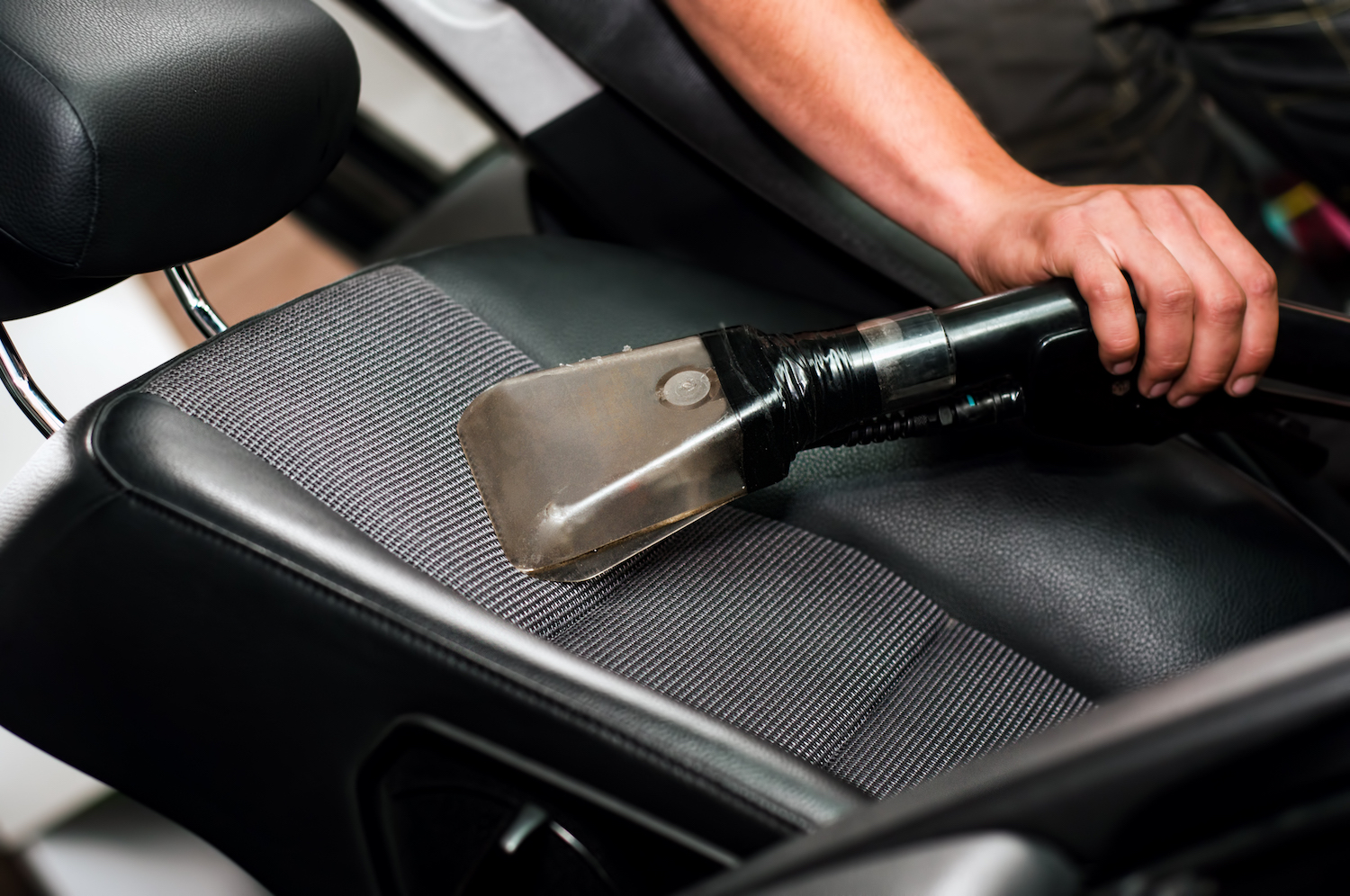 Auto car service cleaning the drivers seat, clealing and vacuuming leather