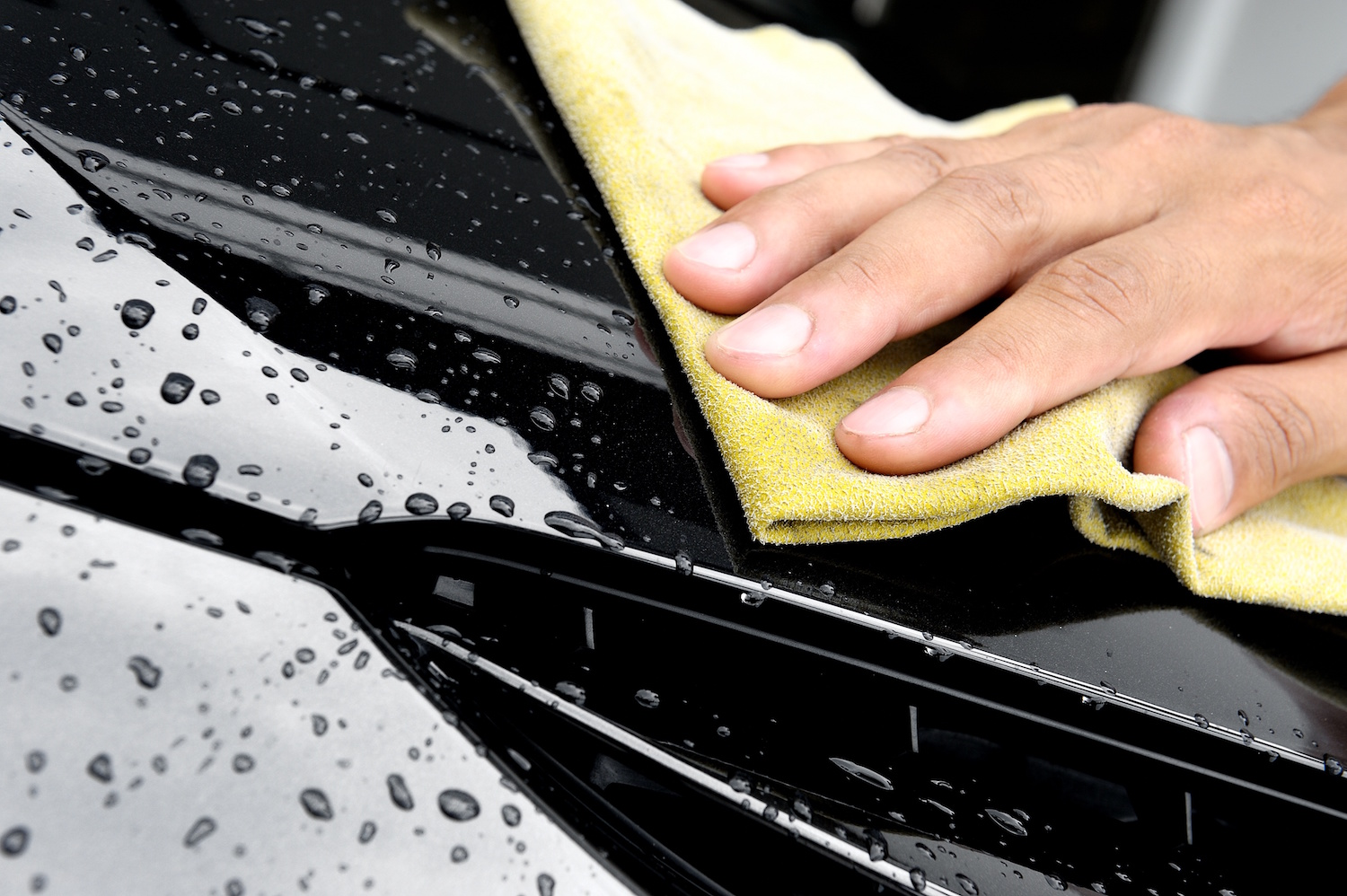hand wiping water on black car